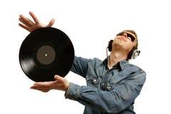 Le DJ dans des écouteurs tord une plaque Photographie stock