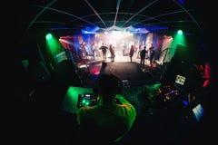 Le DJ dans la musique de mélange de boîte de nuit sur le mélangeur avec des écouteurs et des personnes dansant sur la piste de da Photos libres de droits