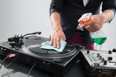 Le DJ dans le smoking nettoyant sa plaque tournante Photo stock