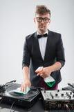 Le DJ dans le smoking nettoyant sa plaque tournante Images libres de droits