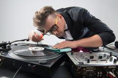 Le DJ dans le smoking nettoyant sa plaque tournante Image stock
