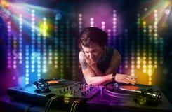 Le DJ jouant des chansons dans une disco avec l'exposition légère photos stock