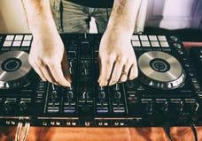Le DJ jouant la musique au plan rapproché et aux mélanges de mélangeur la voie dans la boîte de nuit images libres de droits
