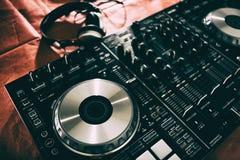Le DJ jouant la musique au plan rapproché et aux mélanges de mélangeur la voie dans la boîte de nuit image stock
