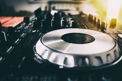 Le DJ jouant la musique au plan rapproché et aux mélanges de mélangeur la voie dans la boîte de nuit photographie stock libre de droits