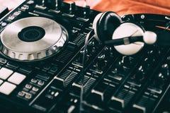 Le DJ jouant la musique au plan rapproché et aux mélanges de mélangeur la voie dans la boîte de nuit photo stock