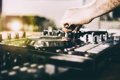 Le DJ jouant la musique au plan rapproché et aux mélanges de mélangeur la voie dans la boîte de nuit images stock