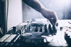 Le DJ jouant la musique au plan rapproch? et aux m?langes de m?langeur la voie dans la bo?te de nuit photos stock