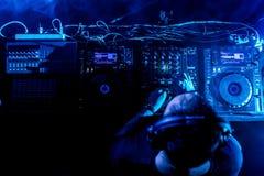 Le DJ jouant la musique de maison et de techno dans une boîte de nuit Mélangeant et commandant la musique photos libres de droits