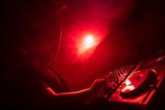 Le DJ jouant la musique de maison et de techno dans une boîte de nuit Mélangeant et commandant la musique photos stock