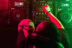 Le DJ jouant la musique de maison et de techno dans une boîte de nuit Mélangeant et commandant la musique photographie stock libre de droits