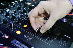 Le DJ jouent sur la console sonore de mélangeur Photos stock