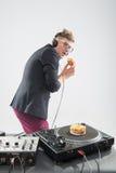 Le DJ mangeant le beignet sur la plaque tournante de lieu de travail Images libres de droits