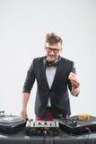 Le DJ mangeant le beignet sur la plaque tournante de lieu de travail Photo libre de droits