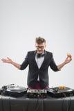 Le DJ mangeant le beignet sur la plaque tournante de lieu de travail Image libre de droits