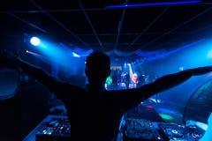 Le DJ ont ajusté ses mains sur le mélangeur et à télécommande la musique dans la boîte de nuit de disco Photos stock