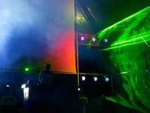 Le DJ sur l'étape à l'intérieur des rayons de laser Photos stock