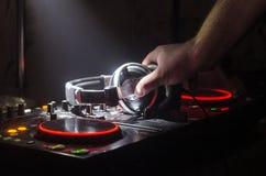 Le DJ tournant, se mélangeant, et rayant dans une boîte de nuit, des mains du DJ tordent de divers contrôles de voie sur la plate images stock