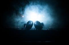 Le DJ tournant, se mélangeant, et rayant dans une boîte de nuit, des mains du DJ tordent de divers contrôles de voie sur la plate photo stock