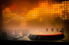 Le DJ tournant, se mélangeant, et rayant dans une boîte de nuit, des mains du DJ tordent de divers contrôles de voie sur la plate Photographie stock