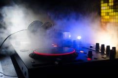 Le DJ tournant, se mélangeant, et rayant dans une boîte de nuit, des mains du DJ tordent de divers contrôles de voie sur la plate Photos libres de droits
