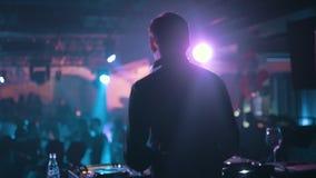 Le DJ tourne les disques à la boîte de nuit moderne, vue arrière, mouvement lent banque de vidéos