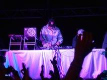 Le DJ tourne sur l'étape avec la foule des mains de lancement de personnes en air Photos stock