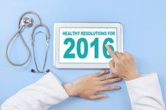 Le docteur écrit la résolution saine pour 2016 sur le comprimé Images stock