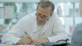 Le docteur écrit une prescription au patient clips vidéos