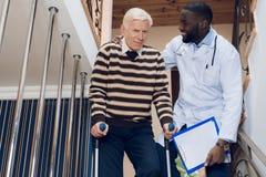 Le docteur aide un homme à descendre les escaliers dans une maison de repos Photo stock