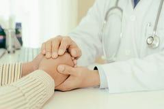 Le docteur amical d'homme remet tenir la main patiente se reposant au De Photos libres de droits