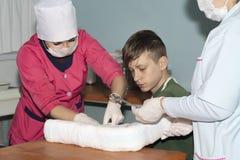 Le docteur bande un bras cassé à un garçon photo libre de droits