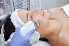 Le docteur-cosmetologist fait à l'appareil une procédure du nettoyage d'ultrason de la peau faciale photos libres de droits