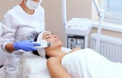 Le docteur-cosmetologist fait à l'appareil une procédure du nettoyage d'ultrason de la peau faciale d'un beau, jeune femme image stock