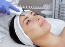 Le docteur-cosmetologist fait à l'appareil une procédure du nettoyage d'ultrason de la peau faciale d'un beau, jeune femme photo libre de droits