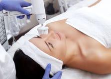 Le docteur-cosmetologist fait à l'appareil une procédure du nettoyage de visage de matériel avec une brosse tournante molle d'un  photo libre de droits