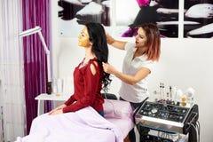 le Docteur-cosmetologist fait à la procédure la thérapie microcurrent sur des cheveux de femme photographie stock libre de droits