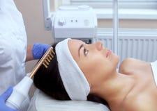 Le docteur-cosmetologist fait la thérapie de Microcurrent de procédure sur les cheveux d'un beau, jeune femme dans un salon de be image libre de droits