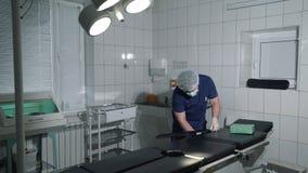 Le docteur dans l'hôpital ajuste la table chirurgicale Le chirurgien prépare pour la chirurgie une table et un matériel médical d banque de vidéos