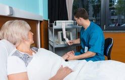 Le docteur dans l'uniforme regarde l'analyse de l'électrocardiographe e Photos stock