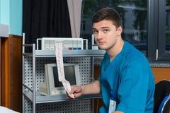 Le docteur dans l'uniforme tient l'analyse de l'examen d'électrocardiographe Photographie stock libre de droits