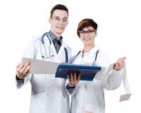 Le docteur de deux jeunes tenant un électrocardiogramme fait face à l'appareil-photo Photos libres de droits