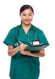 Le docteur de femme écrivent sur le presse-papiers Photo stock