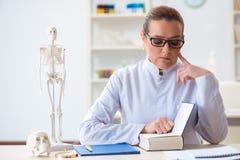 Le docteur de femme étudiant le squelette humain photos stock