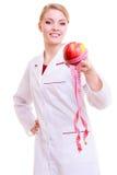 Le docteur de femme avec la mesure attache du ruban adhésif au fruit. régime. Photo libre de droits