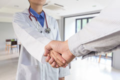 Le docteur de femme serre la main au patient dans l'hôpital photographie stock