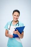 Le docteur de jeune femme frotte dedans avec un stéthoscope pédiatrique noir tenant le comprimé bleu pour des papiers Images stock