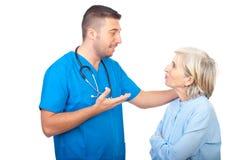 Le docteur de soin donnent l'explication au femme aîné Image libre de droits