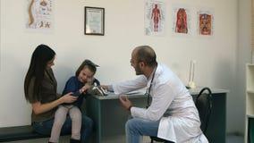 Le docteur de sourire donnant le jouet de lapin pour encourager a dérangé la patiente de petite fille banque de vidéos