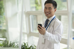 Le docteur de sourire employant le sien téléphonent dans le lobby d'hôpital, regardant l'appareil-photo, les portes en verre Photos stock